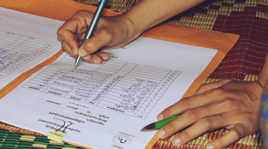 マイクロファイナンスの高校生ボランティアが書類の記録をサポート